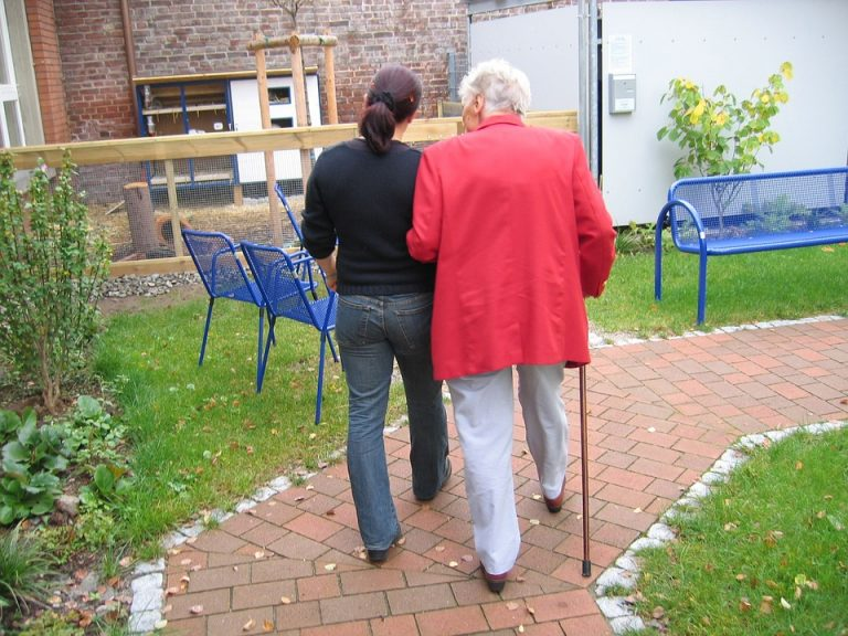 Dependent Woman with Dementia walking with her Daughter on a Nursing Home