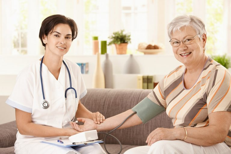 Nurse measuring blood pressure of senior woman at home Looking at camera smiling on a Nursing Home