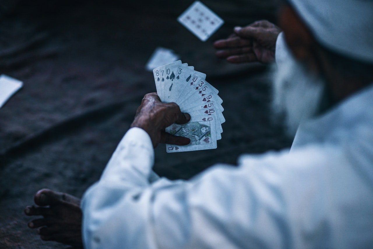 old man holding playing cards