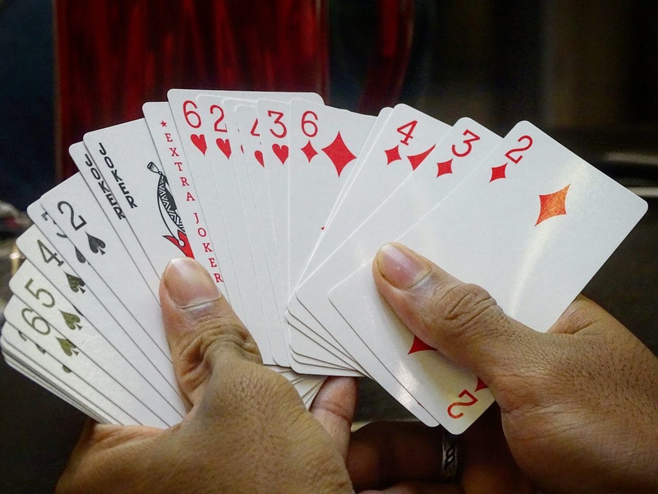 playing cards held by two hands