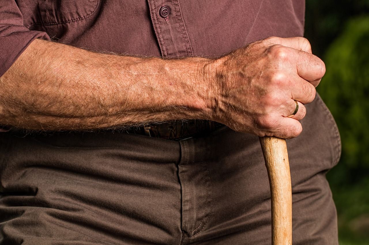 a senior's hand holding a stick or cane