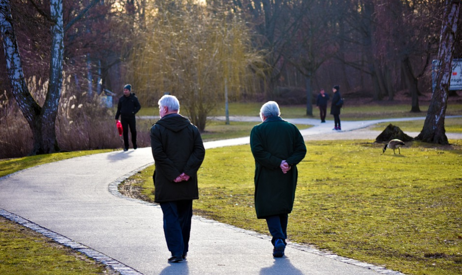 two elderly walking in a park