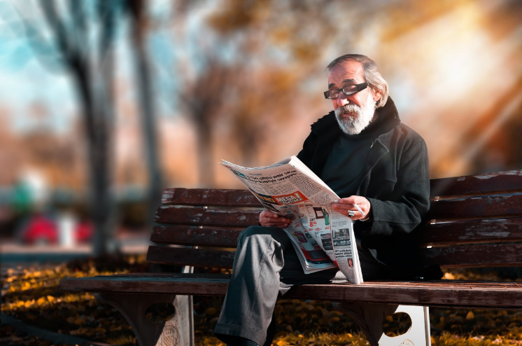 old man reading newspaper sitting in a wooden bench